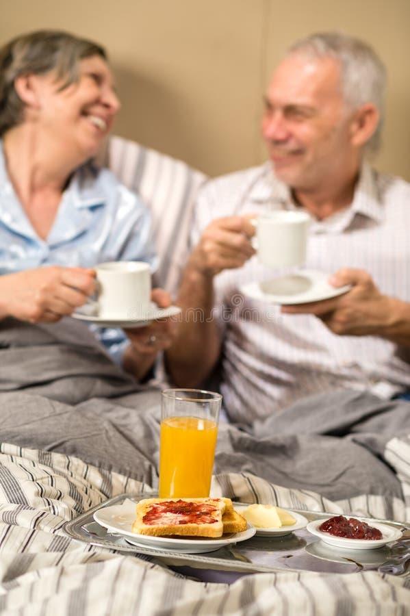 Зрелые пары наслаждаясь завтраком на гостиничном номере стоковое фото rf