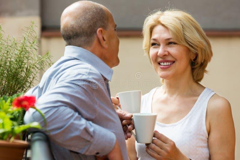 Зрелые пары на балконе с кофе стоковое изображение