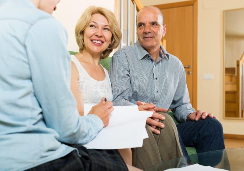 Зрелые пары обсуждая детали частного страхования с agen стоковая фотография rf