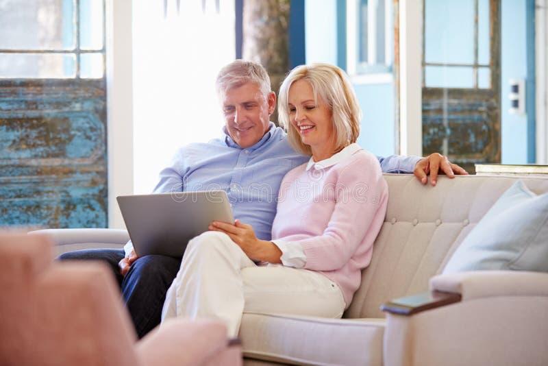 Зрелые пары дома в салоне используя портативный компьютер стоковые изображения rf