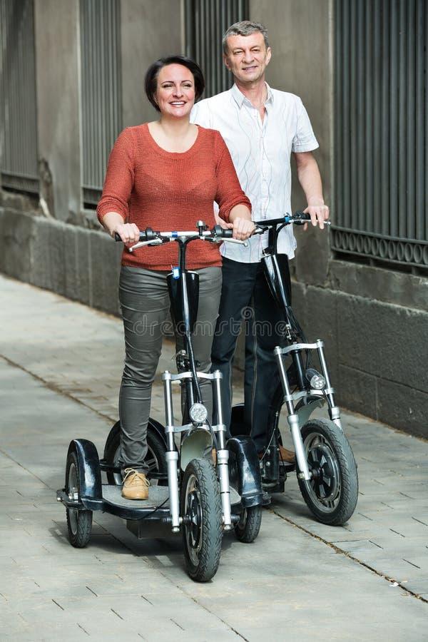 Зрелые пары оставаясь с электрическими велосипедами стоковые изображения rf