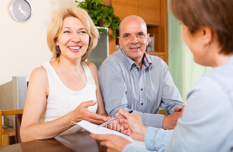 Зрелые пары пенсионеров разговаривая с работником стоковые фото