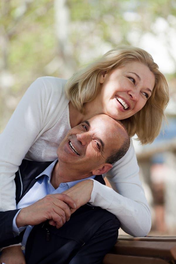 Зрелые пары семьи оставаясь внешний на дне и усмехаться падения стоковые изображения
