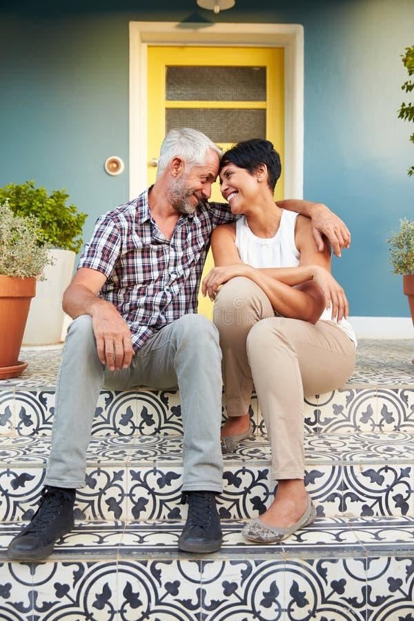 Зрелые пары сидя на шагах вне дома стоковое фото