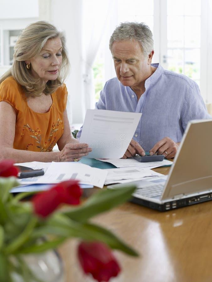 Зрелые пары с счетами, калькулятором и компьтер-книжкой стоковое изображение