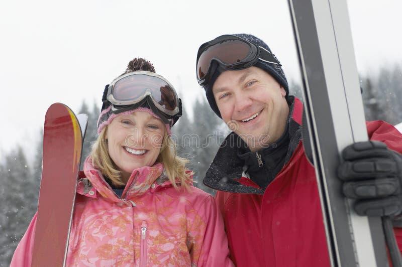 Зрелые пары с лыжей и стеклами стоковые изображения
