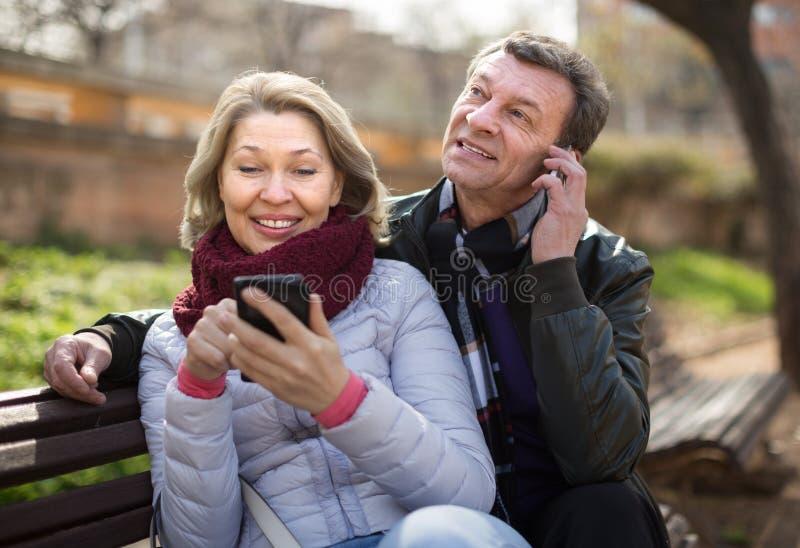 Зрелые пары с smartphones на скамейке в парке стоковое изображение rf