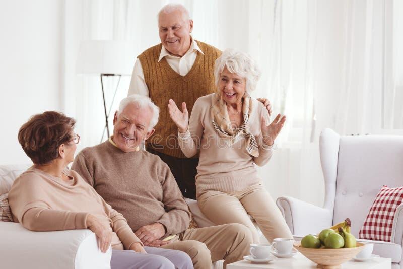 Зрелые друзья говоря и усмехаясь стоковое фото rf