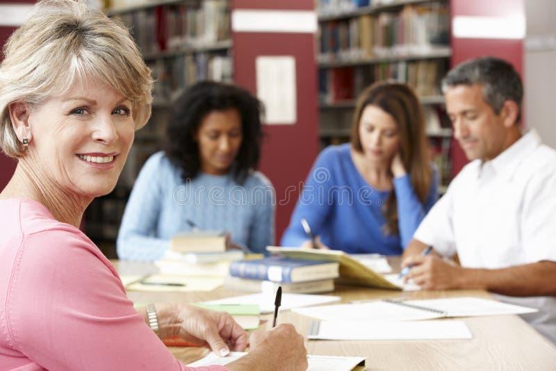 Зрелые студенты работая в библиотеке стоковые изображения