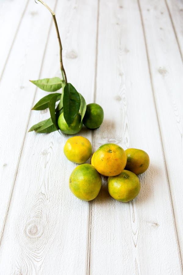 Зрелые сладостный лимон и tangerine с листьями на деревянной доске стоковое фото rf