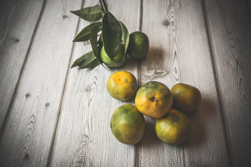 Зрелые сладостный лимон и tangerine с листьями на деревянной доске стоковая фотография rf