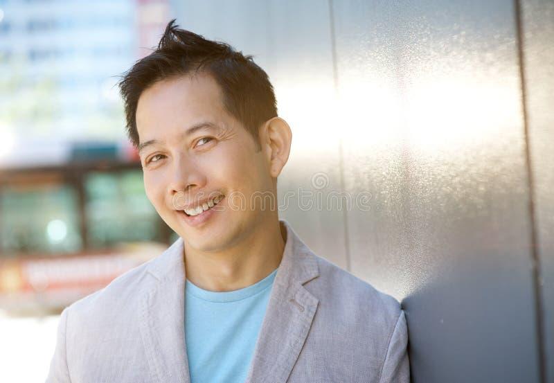 Зрелый азиатский человек усмехаясь outdoors стоковое изображение rf