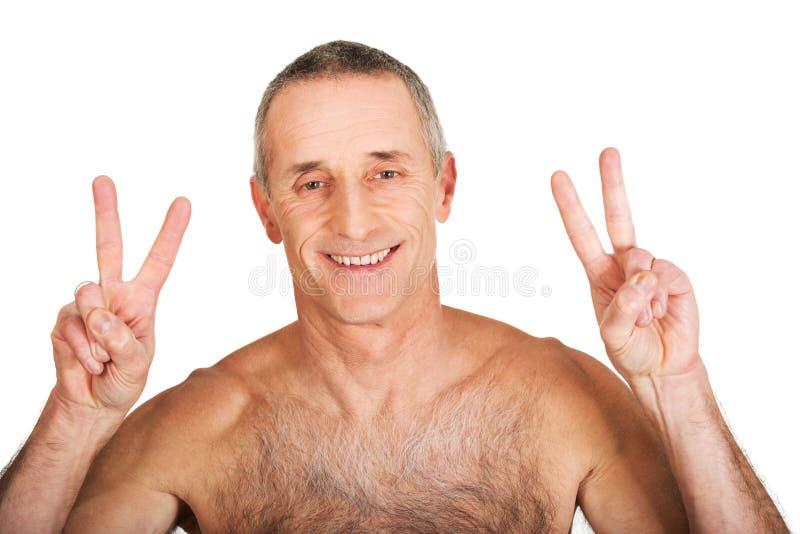 Зрелый без рубашки человек с знаком победы стоковые изображения