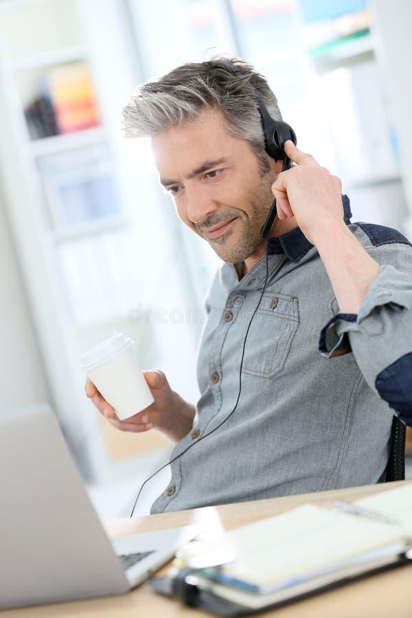 Зрелый бизнесмен звоня видео- на интернете стоковые фотографии rf