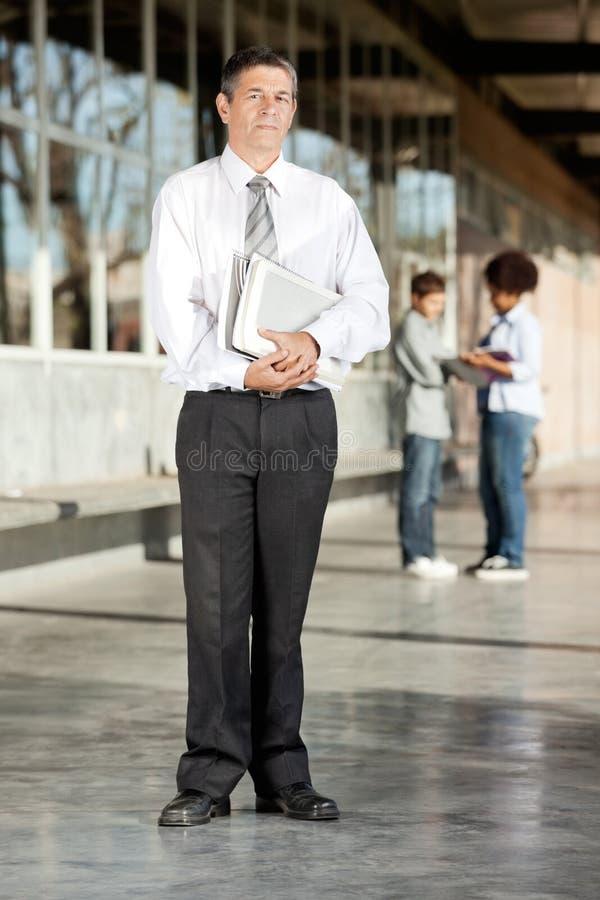 Зрелый коллеж профессора С Книги Standing На стоковые изображения rf