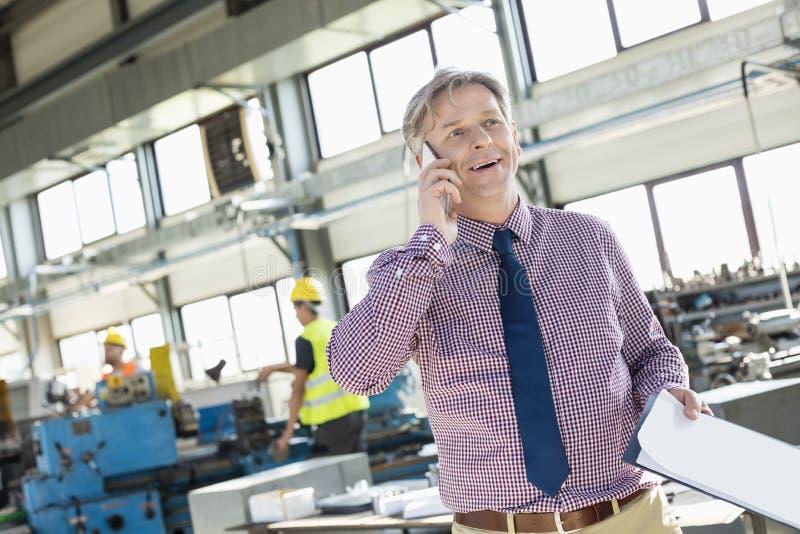 Зрелый мужской заведущая с доской сзажимом для бумаги говоря на мобильном телефоне в индустрии стоковая фотография rf