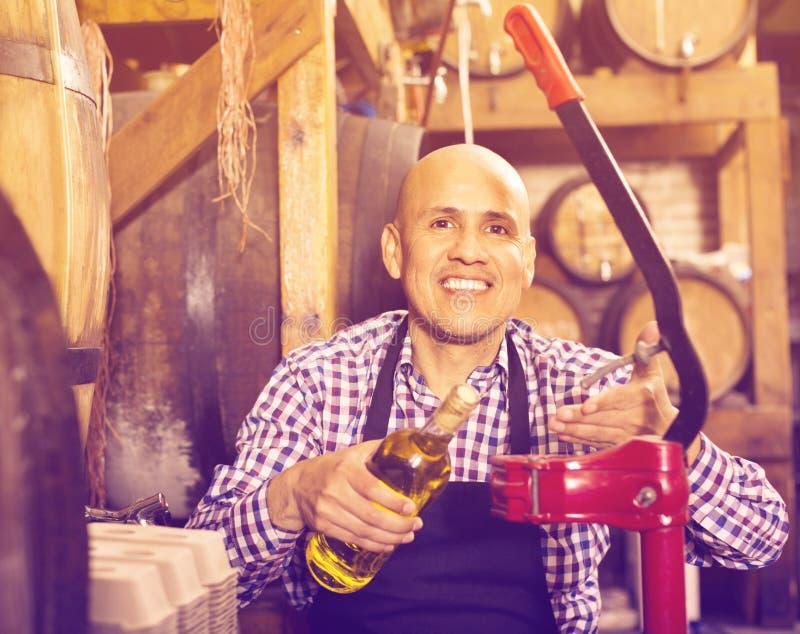 Зрелый мужской создатель вина corking бутылка вина стоковое изображение rf