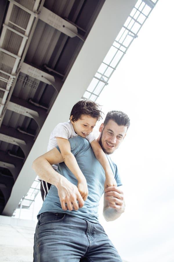 Зрелый отец с его сыном под мостом имея семью потехи совместно счастливую, концепцию людей образа жизни стоковое фото