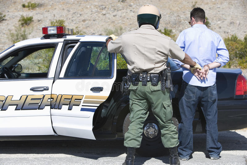 Зрелый офицер движения арестовывая человека стоковое изображение