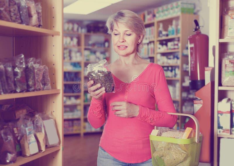 Зрелый покупатель женщины ища для здоровой еды стоковая фотография rf