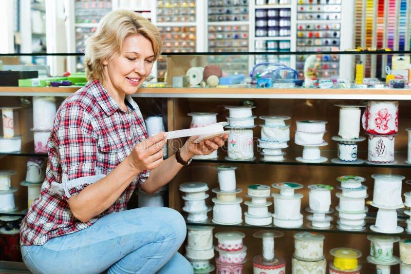 Зрелый радостный клиент женщины выбирая различную ленту стоковое изображение