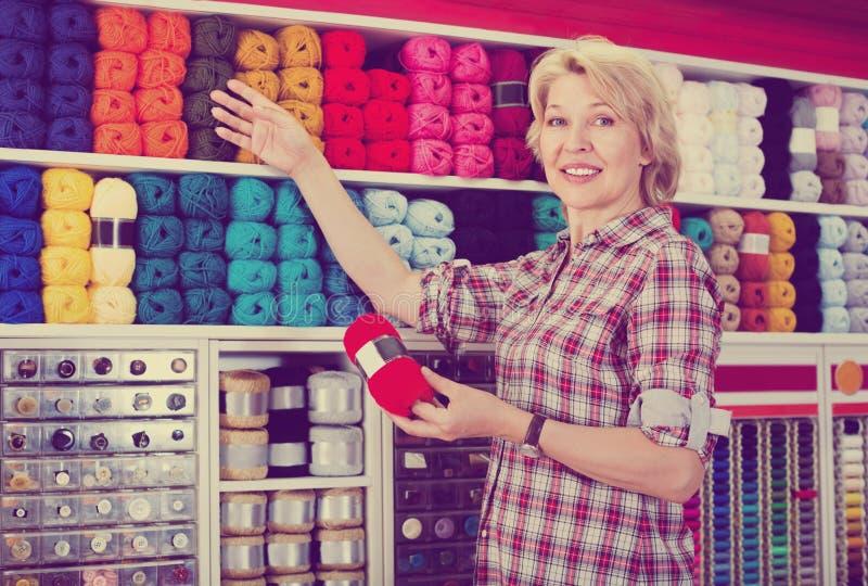 Зрелый радостный клиент женщины выбирая различную пряжу стоковое изображение