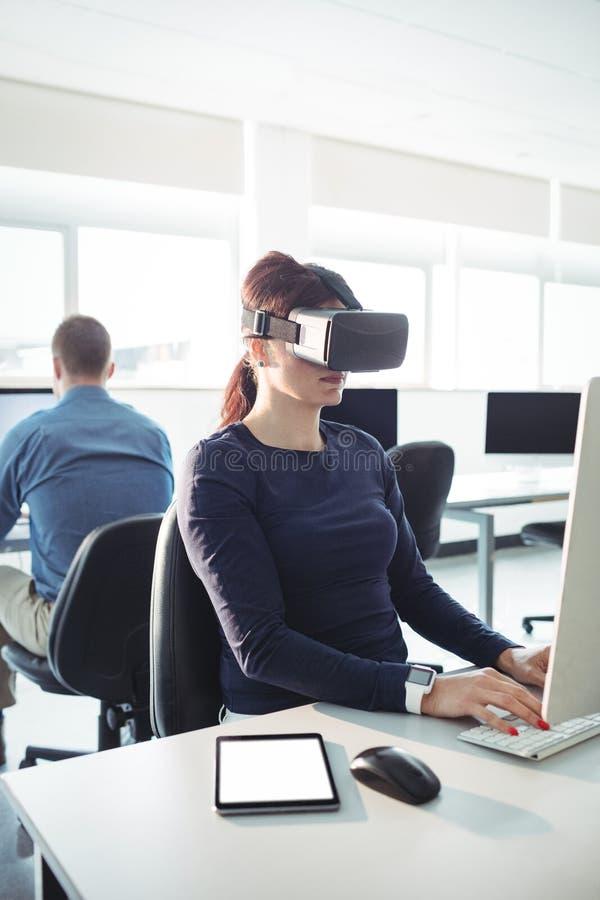 Зрелый студент в шлемофоне виртуальной реальности используя компьютер стоковые изображения rf