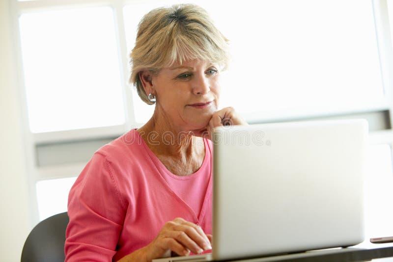 Зрелый студент используя компьютер в классе стоковая фотография rf