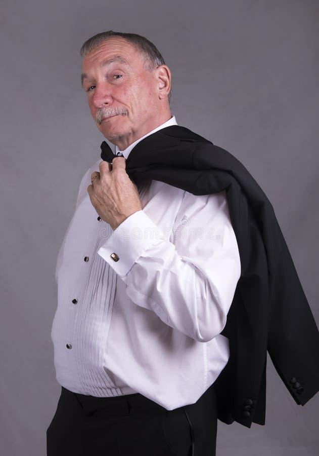 Зрелый человек в костюме, держа куртку обедающего стоковая фотография