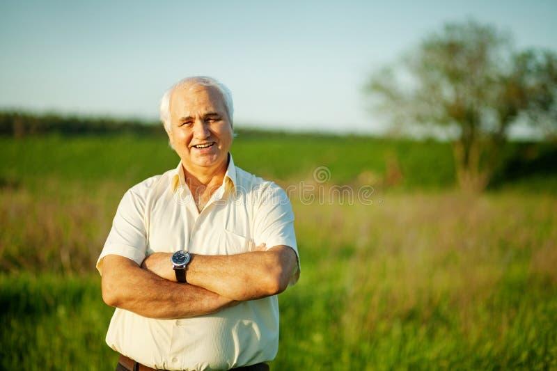 Зрелый человек идя в поле стоковое фото rf