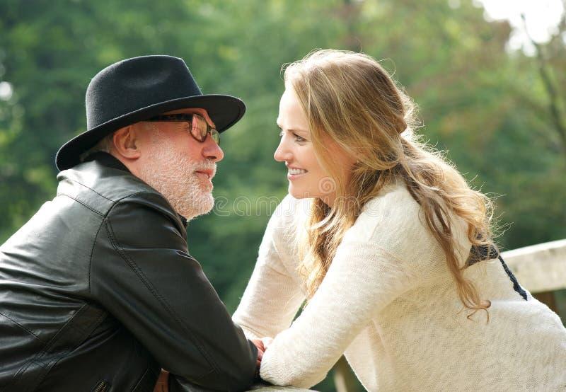Зрелый человек при молодая женщина усмехаясь на одине другого стоковое изображение rf