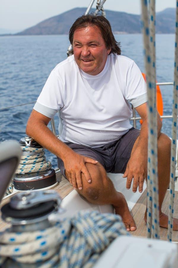 Зрелый человек сидя на яхте плавания Спорт стоковые изображения
