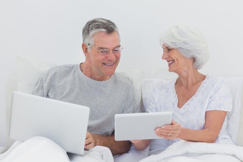 Зрелый человек смотря ПК таблетки wifes стоковое изображение