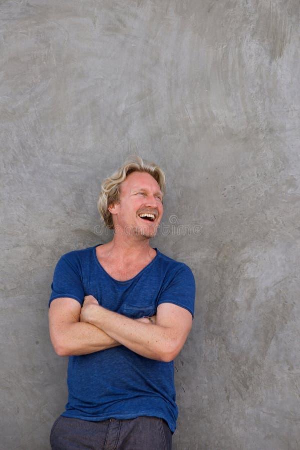 Зрелый человек стоя с пересеченными оружиями и смотря отсутствующий и смеяться над стоковая фотография rf