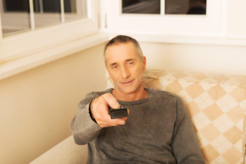Зрелый человек с дистанционным управлением стоковые фото