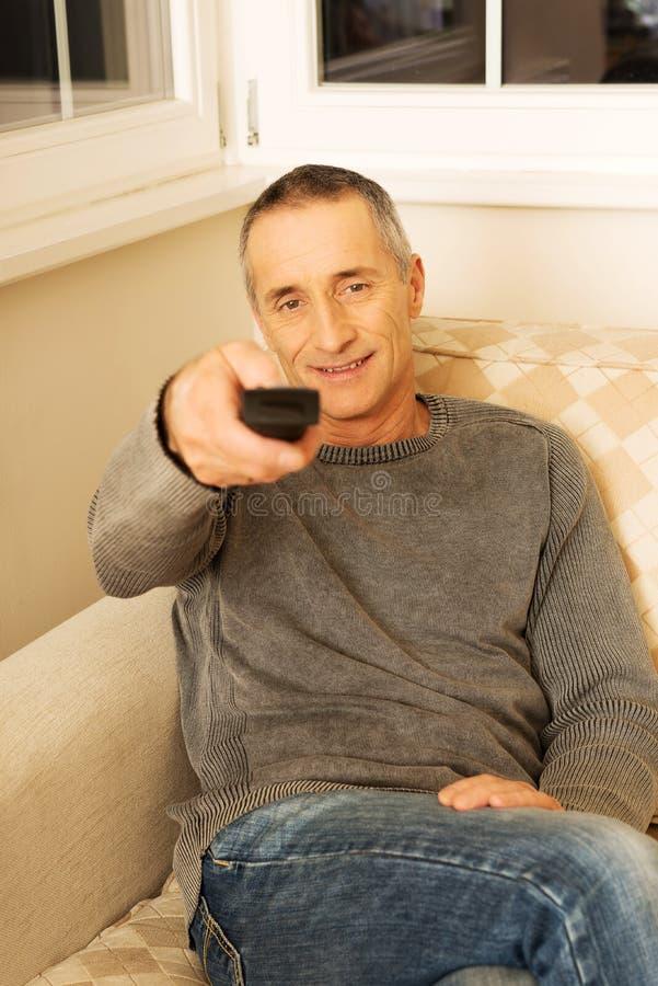 Зрелый человек с дистанционным управлением стоковое фото rf