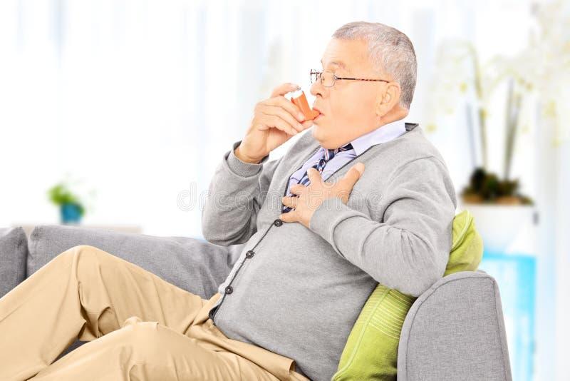 Зрелый человек усаженный на софу принимая обработку астмы дома стоковые фото