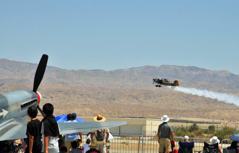 Зрители наблюдая, как самолет-биплан Stearman принял  стоковая фотография