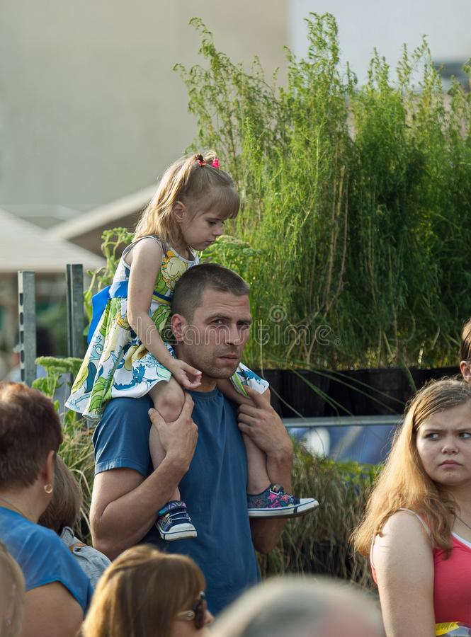 Зритель с девушкой на плечах наблюдает выставку стоковые фотографии rf