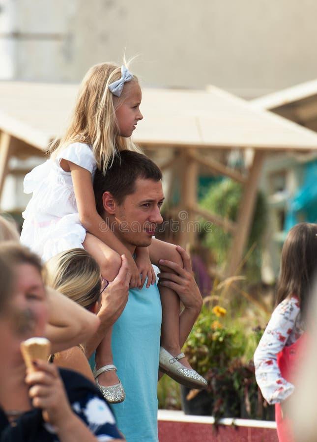 Зритель с девушкой на плечах наблюдает день шоу города Москвы стоковое фото rf