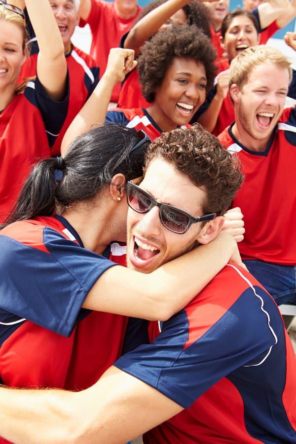 Зрители спорт в цветах команды празднуя стоковое изображение rf