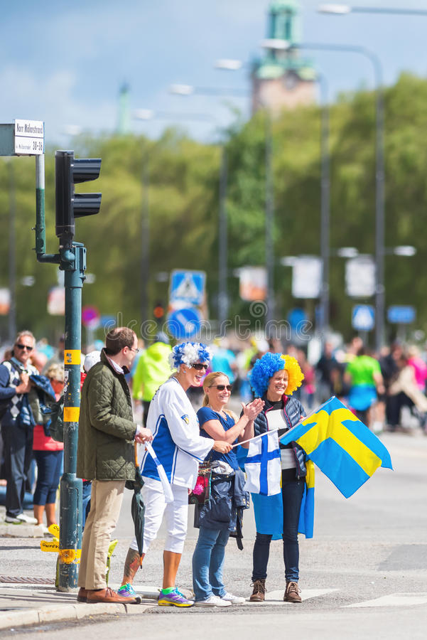 Зрители с шведскими и финскими костюмами веселя на беге стоковые фото