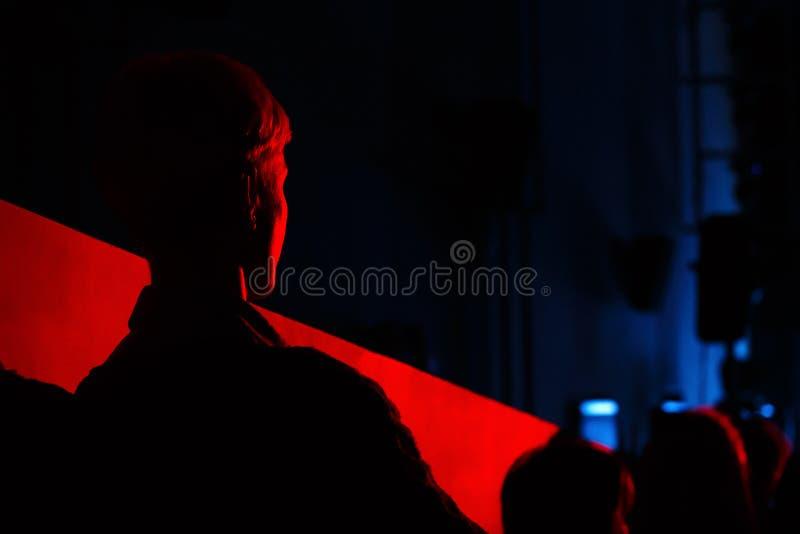 Зритель силуэта облегчен кров-красным светом Детеныши на стоковые изображения