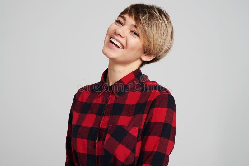 Зубастая усмехаясь женщина в проверенной рубашке смотря камеру стоковое изображение