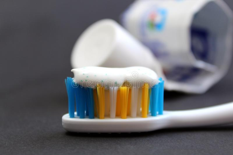 Зубная паста и щетки на черной предпосылке стоковые изображения