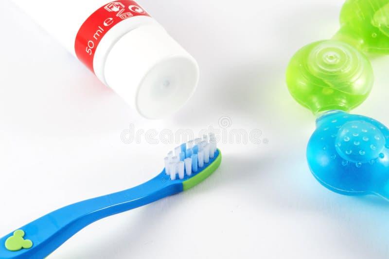 Зубная щетка и зубная паста младенца на белой предпосылке стоковое изображение