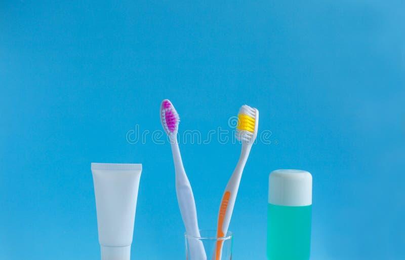 2 зубной щетки в стекле около зубной пасты и rinse против голубой предпосылки стоковое изображение
