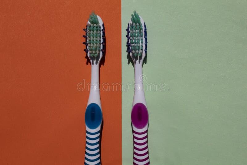 2 зубной щетки, голубой и розовый Изолированный на зеленой и оранжевой предпосылке стоковая фотография