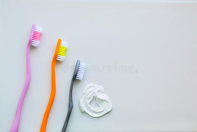3 зубной щетки на белой предпосылке и белой зубной пасте Концепция зубоврачебной гигиены, личной заботы стоковые фото