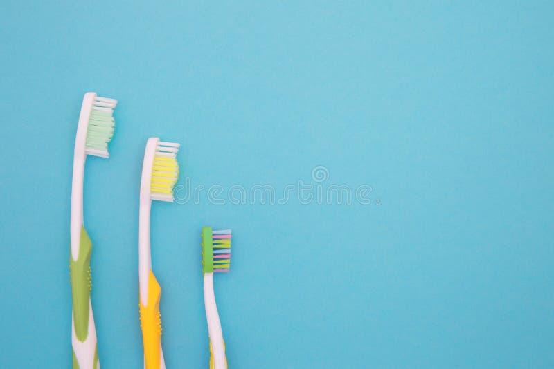 3 зубной щетки на предпосылке голубой бумаги стоковые изображения rf